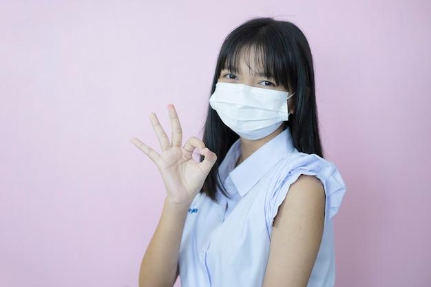 Aziatische student vaccinatie op roze achtergrond.