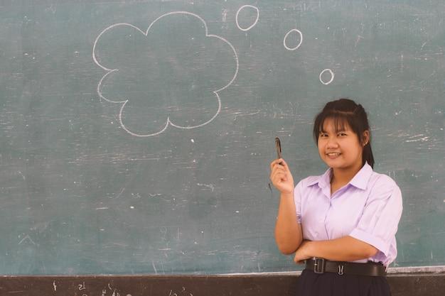 Aziatische studente die en bij blackbord in klaslokaal denken glimlachen.