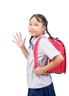 Aziatische studente die naar school gaan en vaarwel geïsoleerd zwaaien