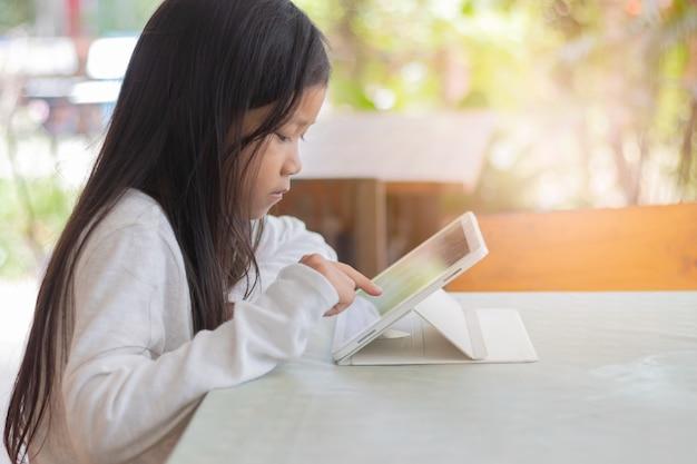 Aziatische studente. gelukkig vrolijk jong aziatisch meisje dat en taplet glimlacht gebruikt