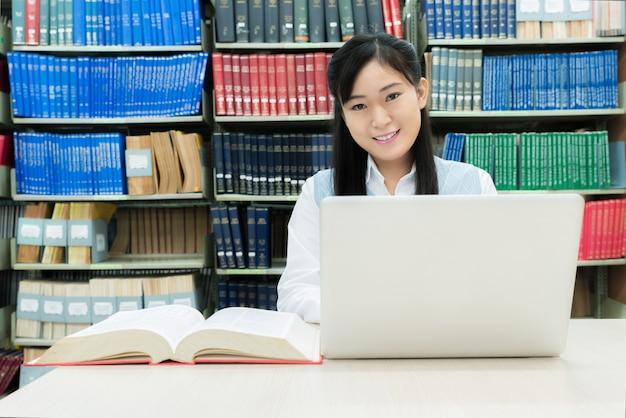 Aziatische studente met laptop en boeken die bij bibliotheek op universiteit werken.