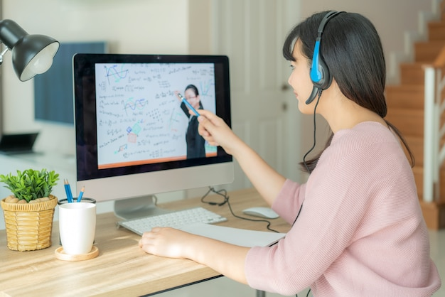 Aziatische studente videoconferentie e-leert met leraar op computer in woonkamer thuis.