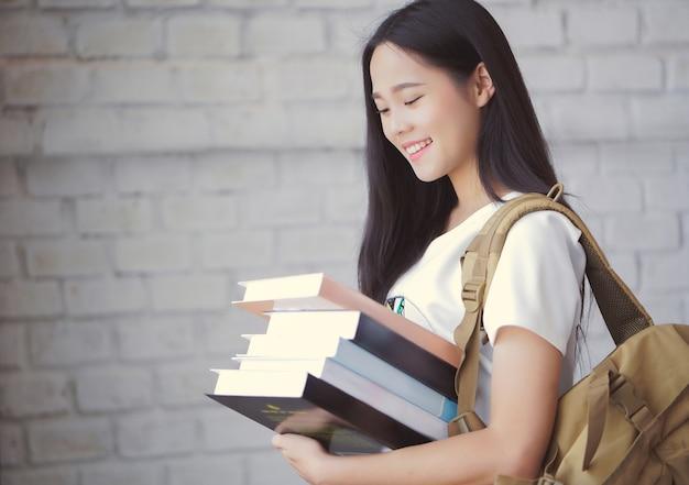 Aziatische studenten die boeken houden op universiteit