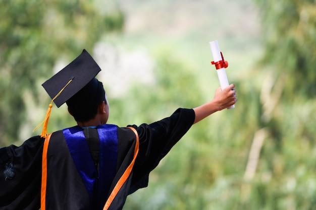 Aziatische studenten droegen zwarte pakjes met stroken, zwarte hoeden, gele kwastjes op de afstudeerdag.