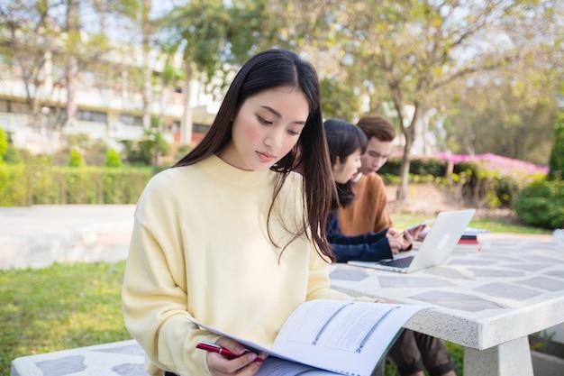 Aziatische studenten gebruiken notebooks en tablets om thuis in de tuin te werken en te studeren tijdens de coronavirusepidemie en quarantaine thuis