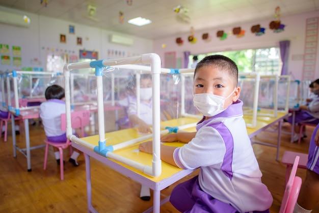 Aziatische studenten in kleuterklassen op scholen in thailand dragen maskers en sociale afstand in klaslokalen