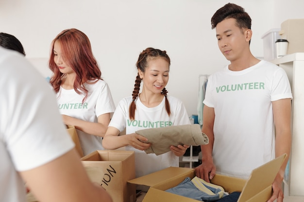 Aziatische studenten in t-shirts van vrijwilligers die kleding in kartonnen dozen inpakken bij het voorbereiden van pakketten voor mensen die hun huis zijn kwijtgeraakt