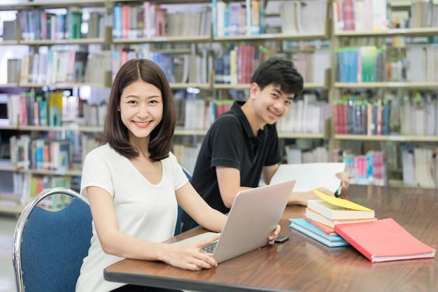 Aziatische studenten met laptop computer en boek die in bibliotheek bij universiteit spreken.