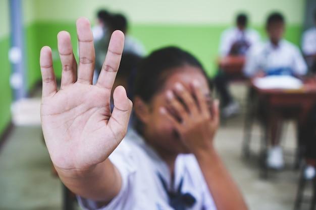 Aziatische studenten raspende handen die zijn gezicht bedekken hulpeloos lijden intimidatie.