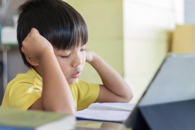 Aziatische studentenjongen die een slimme pad of tablet gebruikt en aanraakt om zijn huiswerk te maken
