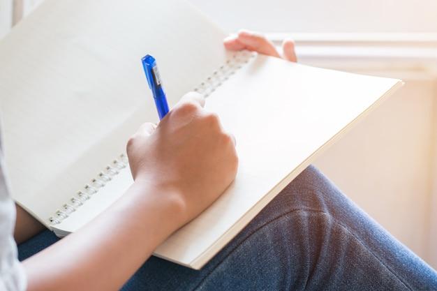 Aziatische studentennota over notitieboekje terwijl het leren van online studie of e-leert