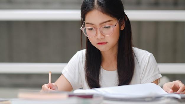 Aziatische studentenvrouw die boeken leest in bibliotheek aan de universiteit