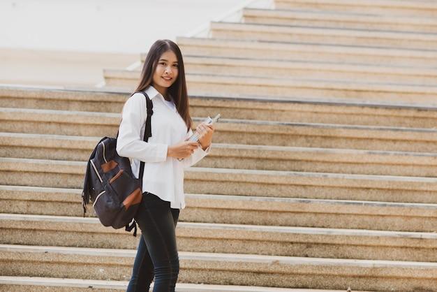 Aziatische studentenvrouw met laptop en zak, onderwijsconcept