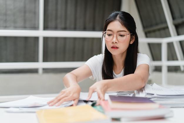 Aziatische studentenvrouwen die boeken lezen in bibliotheek aan de universiteit