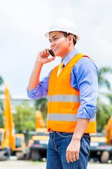 Aziatische supervisor die op bouwwerf telefoneren
