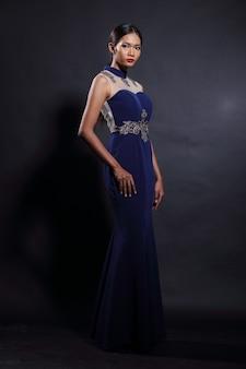 Aziatische tan skin vrouw model in slank diepblauw zijden kant lange avondjurk baljurk, fashion make-up zwart haar, studio verlichting donkere achtergrond, volledige lengte body snap