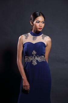 Aziatische tan skin vrouw model in slanke deep blue silk kant lange avondjurk bal jurk, fashion make-up zwart haar, studio verlichting donkere achtergrond, portret halve lichaam kopie ruimte