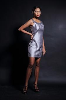 Aziatische tan skin vrouw model in slanke zilveren zijde korte avondjurk baljurk, fashion make-up zwart haar, studio verlichting donkere achtergrond, volledige lengte body snap
