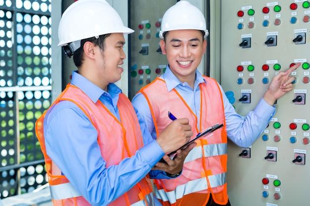 Aziatische technici bij paneel op bouwwerf