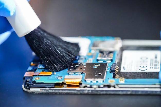 Aziatische technicus reparatie en schoonmaak vuile micro circuit hoofdbord van smartphone met borstel.