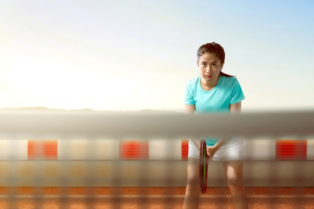 Aziatische tennisspeler vrouw met tennisracket in haar handen