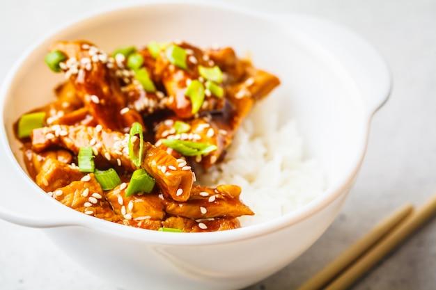 Aziatische teriyakikip met rijst, sesam en groene uien in witte kom.