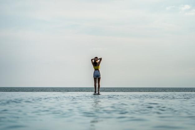 Aziatische thaise tiener vrouw in geel ontspannen en zwemmen pak is posten op de infinity pool naast de zee strand in thailand resort.