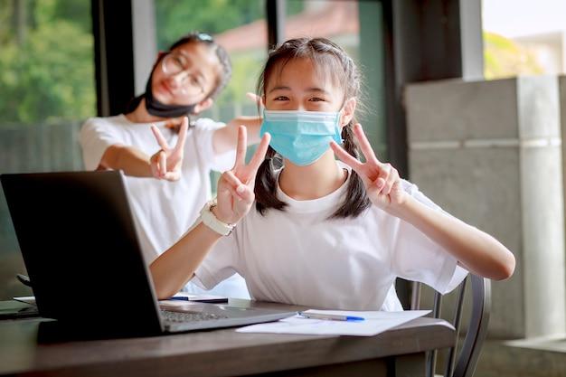 Aziatische tiener die beschermingsmasker draagt dat aan computerlaptop thuis werkt