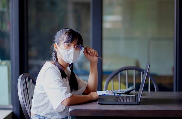 Aziatische tiener die computerlaptop in huiswoonkamer met behulp van