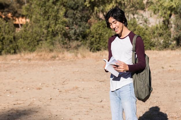 Aziatische tiener die door boek wegknippen