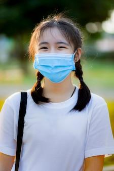 Aziatische tiener die een beschermingsmasker draagt dat buiten staat met een blij gezicht