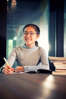 Aziatische tiener die het werk van het schoolhuis in bibliotheekruimte doet
