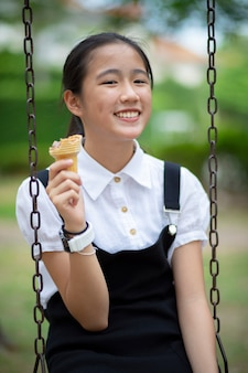 Aziatische tiener die roomijskegel met gelukgezicht eet in groen park