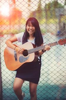 Aziatische tiener die spaanse gitaar met gelukemotie speelt