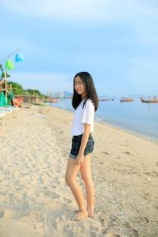 Aziatische tiener die zich met het ontspannen op overzees strand bevindt