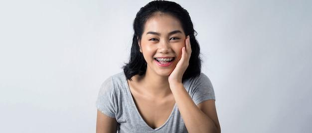 Aziatische tiener gezichtsbehandeling met beugels en lachend naar camera om tandheelkundige orthodontische tanden te tonen die professioneel metaaldraadmateriaal van orthodontist bevatten.