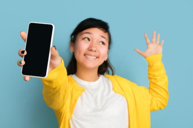 Aziatische tiener portret geïsoleerd op blauwe ruimte. mooi vrouwelijk donkerbruin model met lang haar