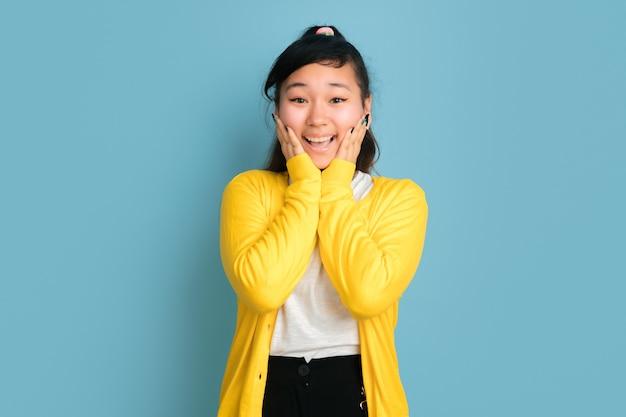 Aziatische tiener portret geïsoleerd op blauwe ruimte