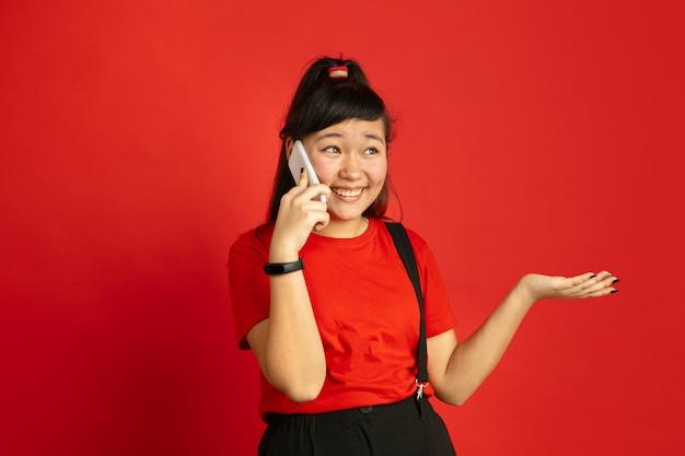 Aziatische tiener portret geïsoleerd op rode ruimte. mooi vrouwelijk donkerbruin model met lang haar in informele stijl