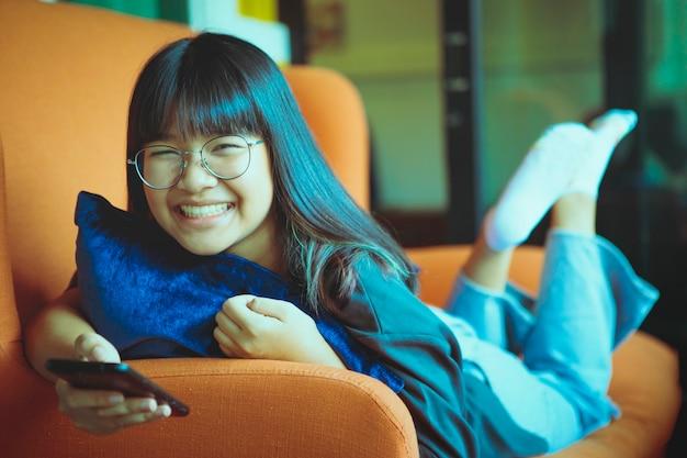Aziatische tiener toothy lachend gezicht liggend op de bank en slimme telefoon in de hand te houden