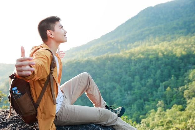 Aziatische tiener zittend op de rand van de klifbrug en kijken naar de berg.