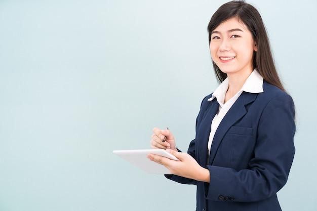 Aziatische tienermeisje in pak met behulp van computer digitale tablet isolaat op blauwe achtergrond
