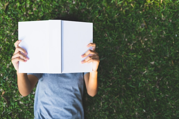 Aziatische tienermeisjes liggen lezen van een boek op het gras in het park
