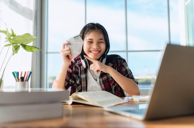 Aziatische tienermeisjesstudent draagt draadloze hoofdtelefoonstudie online met zoomvergadering, gelukkige jonge vrouw leert taal luister lezing bekijk webinar schrijf notities en kijk naar laptop afstandsonderwijs.