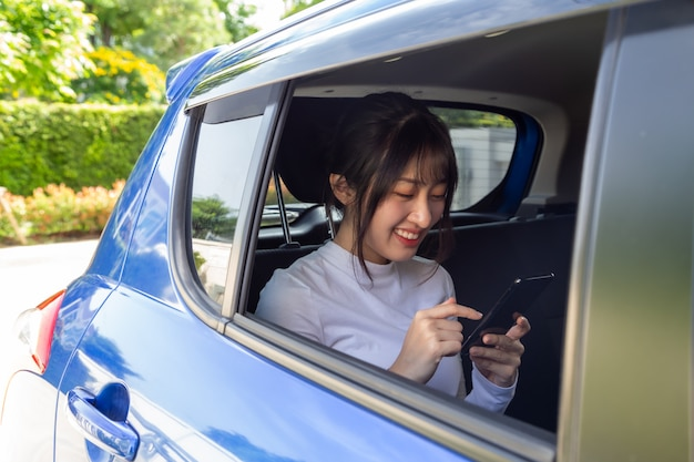 Aziatische tienervrouw die een smartphone in achterbank van auto gebruiken