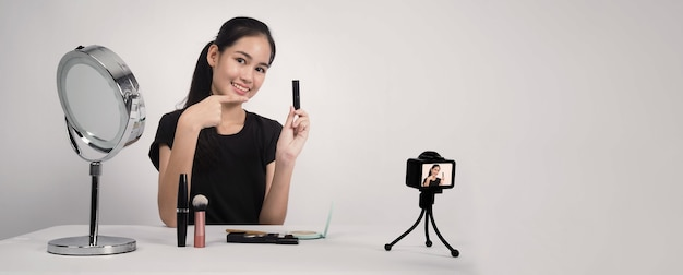 Aziatische tienervrouw zit voor de camera en live-uitzendingen als beautyblogger-influencer of youtuber om te bekijken of advies te geven over hoe ze thuis het goed kan maken.