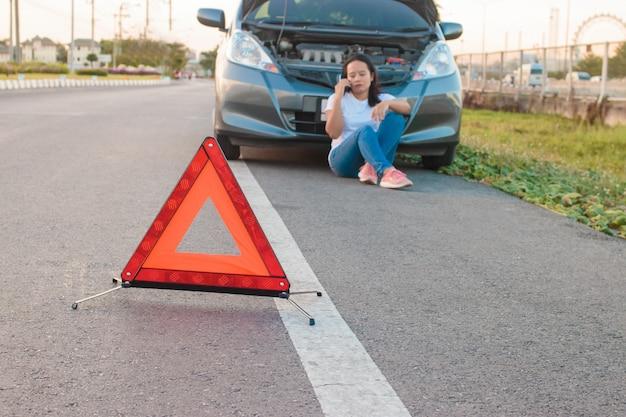 Aziatische tienervrouwen die een mobiele telefoon houden die rond de auto loopt