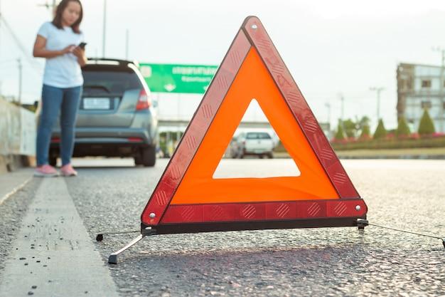 Aziatische tienervrouwen die een mobiele telefoon houden lopend rond de auto, zware stemming tijdens de avonduren. langs de snelweg omdat haar auto kapot is gegaan en ze wacht op hulp van iemand.