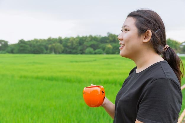 Aziatische tienervrouwen die mok in groene aard houden