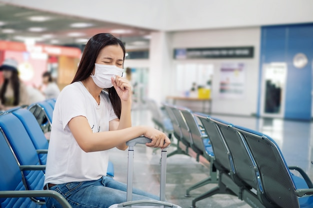 Aziatische toerist die zich ziek voelt, hoest, een masker draagt om tijdens de reistijd op de luchthaventerminal te voorkomen ter bescherming tegen de nieuwe uitbraak van coronavirus 2019